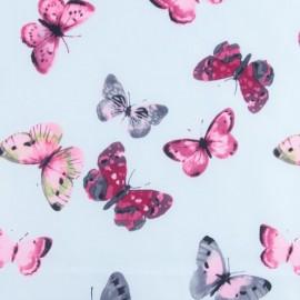 Tissu déperlant souple Envolée de papillons - bleu ciel x 10cm